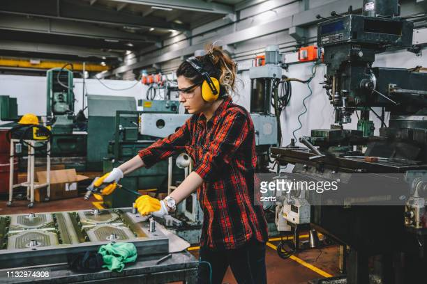 young female lathe worker working with blow gun in factory - blowpipe stock pictures, royalty-free photos & images