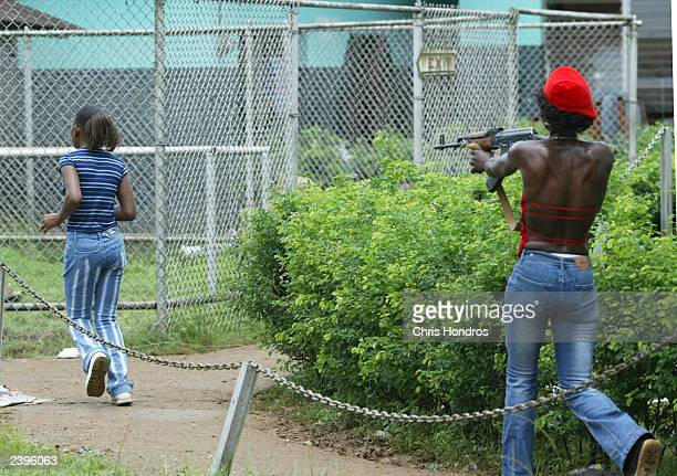 A young female Liberian runs as an armed female LURD rebel soldier chases her with a weapon at the port August 13 2003 in Monrovia Liberia LURD...