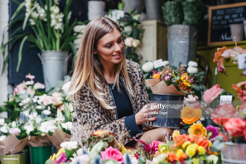 Young female life coach and fashion blogger in leopard print jacket looking at flowers in flower shop in Central London : Stock Photo