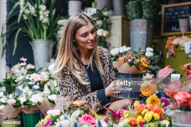 Young female life coach and fashion blogger in leopard print jacket looking at flowers in flower shop in Central London