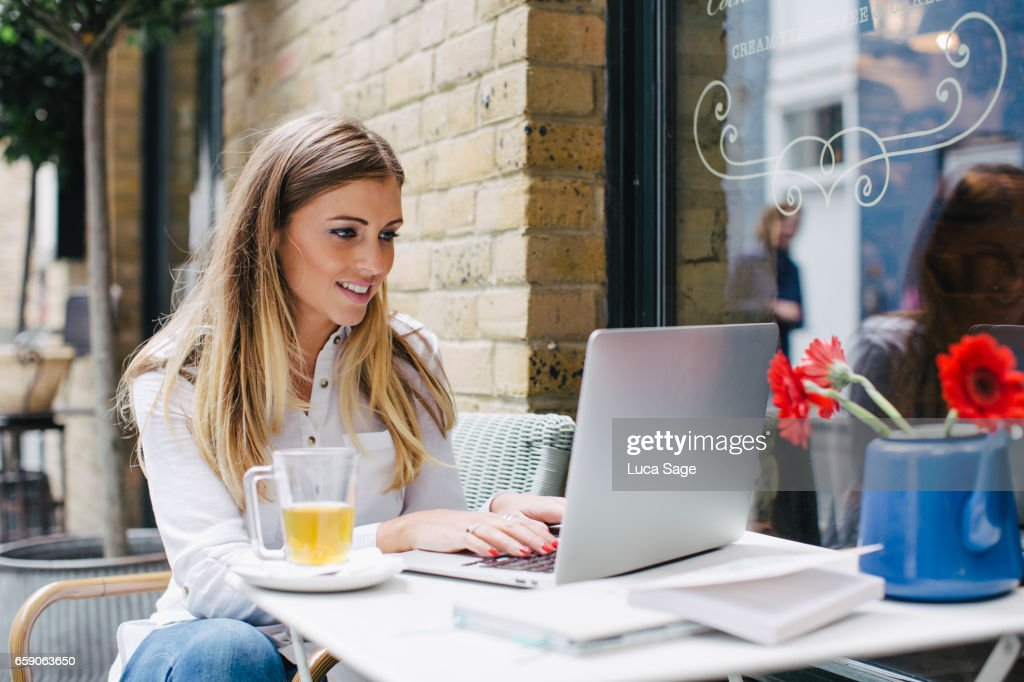 young female life coach blogger typing on laptop in a coffee shop in central London : Stock Photo