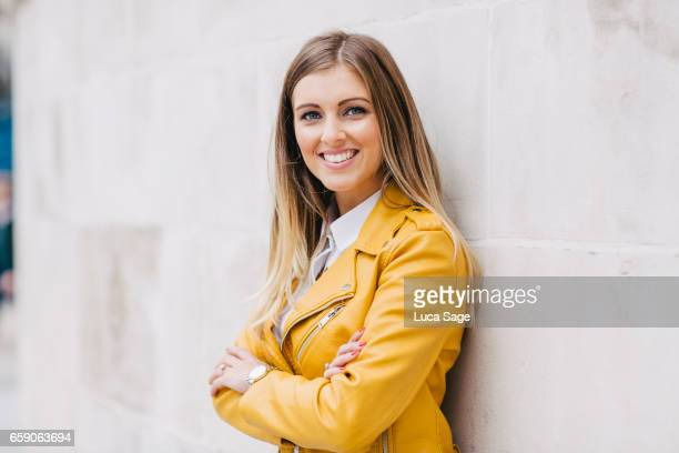 young female lifestyle blogger in bright yellow jacket leaning against wall in central london - jak jas stockfoto's en -beelden