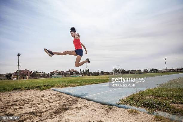 Young female long jumper jumping mid air at sport facility