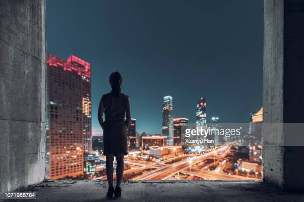 young female looking out over city at night - wolkenkratzer stock-fotos und bilder