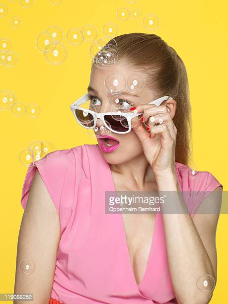 young female looking surprised as bubbles fall
