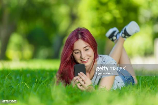 Young female lying in grass and use phone
