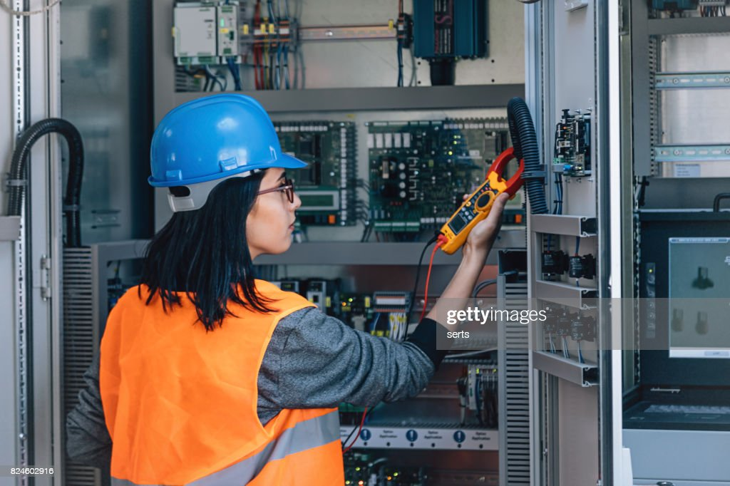 Young female maintenance engineer testing voltage with digital multimeter : Stock Photo