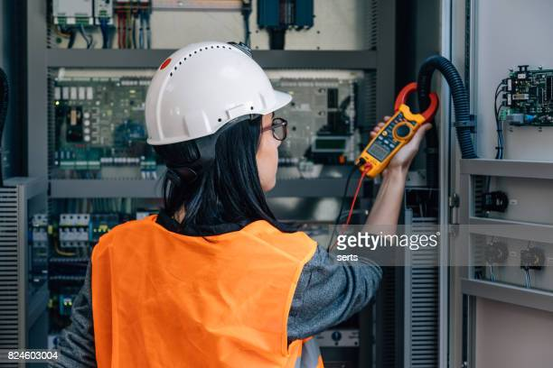 Young female maintenance engineer testing voltage with digital multimeter