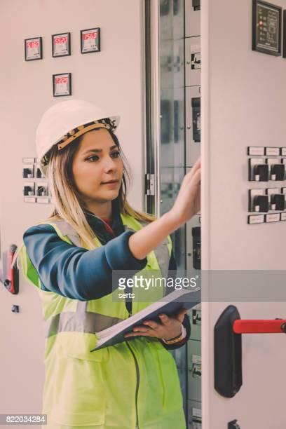 Junge weibliche Instandhalter arbeiten bei Energie-Kontrollraum