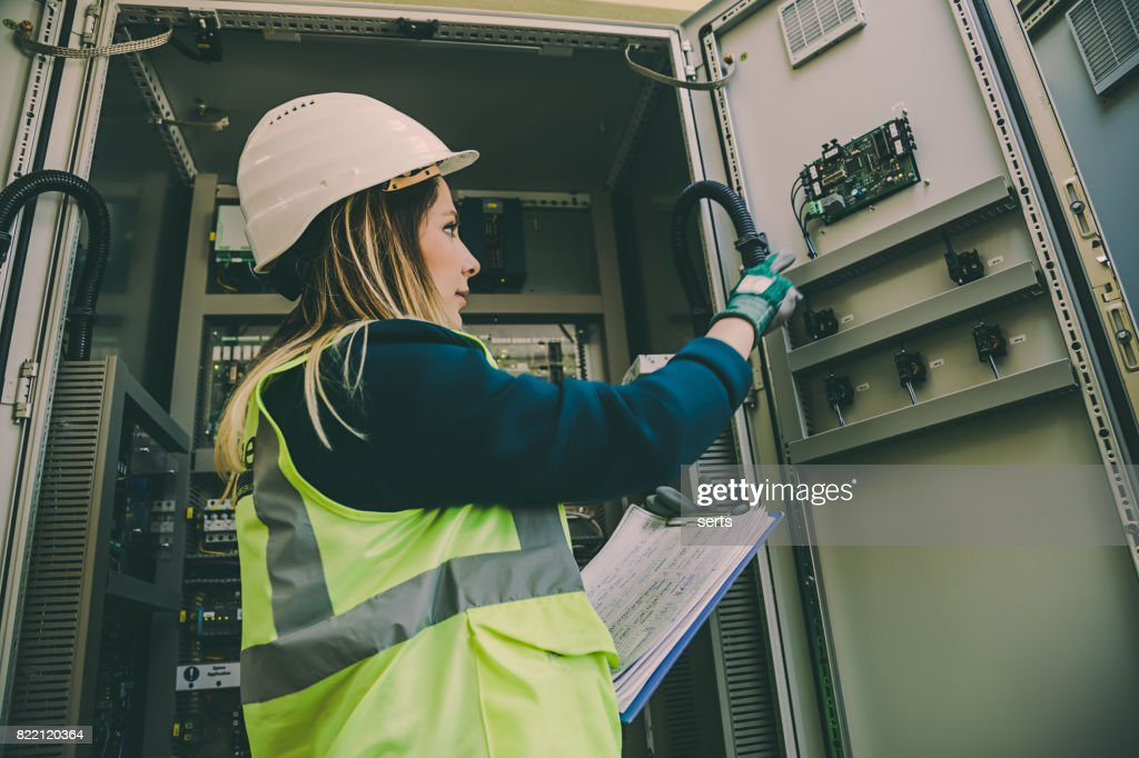 Young female maintenance engineer working at energy control room : Stock Photo