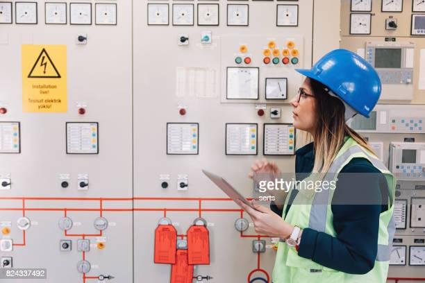 Young female maintenance engineer working at energy control room