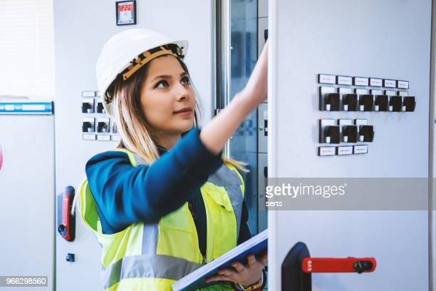 young female maintenance engineer working at energy control room - elettricità foto e immagini stock