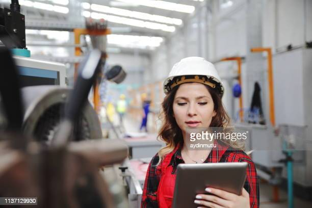young female maintenance engineer working with digital tablet - mechatronics stock pictures, royalty-free photos & images