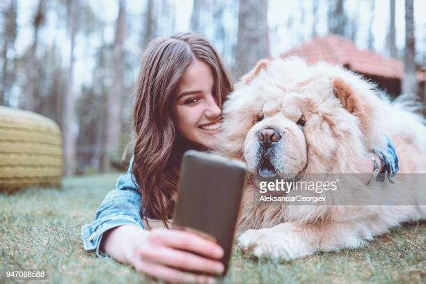 young female making selfie with her chow chow dog in park - chow dog stock pictures, royalty-free photos & images