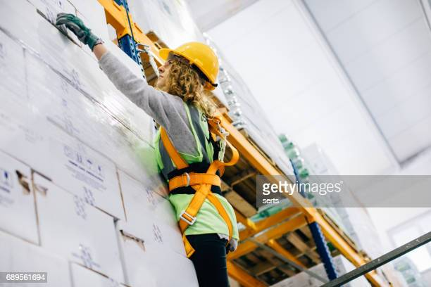 young female manual worker hanging on a climbing rope in warehouse - high up stock photos and pictures