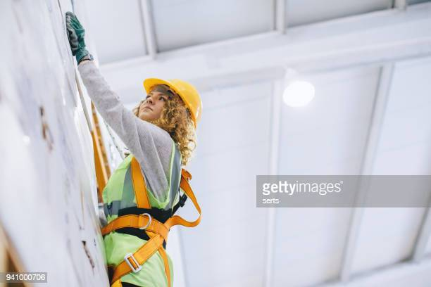 young female manual worker hanging on a climbing rope in warehouse - high up stock pictures, royalty-free photos & images
