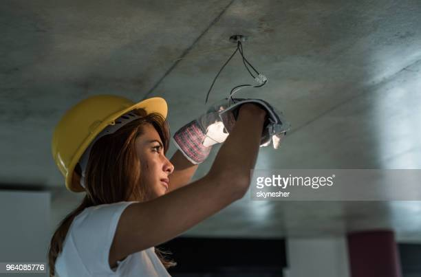 young female manual worker repairing light in renovating apartment. - electrician stock pictures, royalty-free photos & images