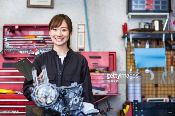 中小企業ガレージにバイクのエンジンを修理する若い女性メカニック。 - 交通事故 ストックフォトと画像