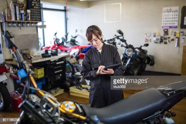 Jonge vrouwelijke monteur herstellen van een motorfiets in haar garage kleine bedrijven.