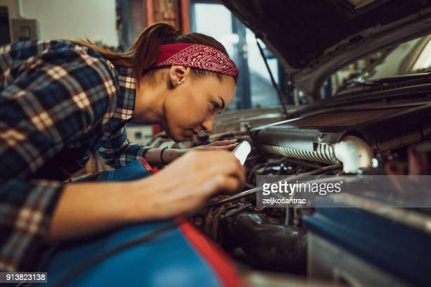 young female mechanic repairing car - adjusting stock pictures, royalty-free photos & images