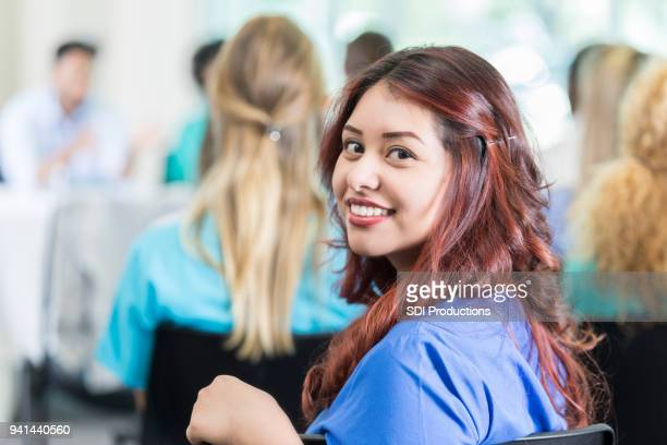 Young female medical student smiles for camera during lecture