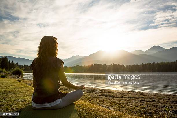Young female meditating by lake.