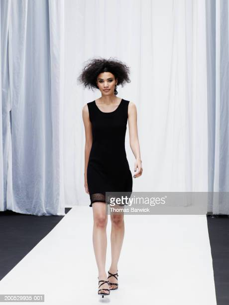 young female model walking down catwalk - catwalk foto e immagini stock