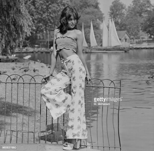 A young female model wears a shirred bandeau boob tube style cropped top with bow motif printed bell bottom high waisted flared trousers and platform...