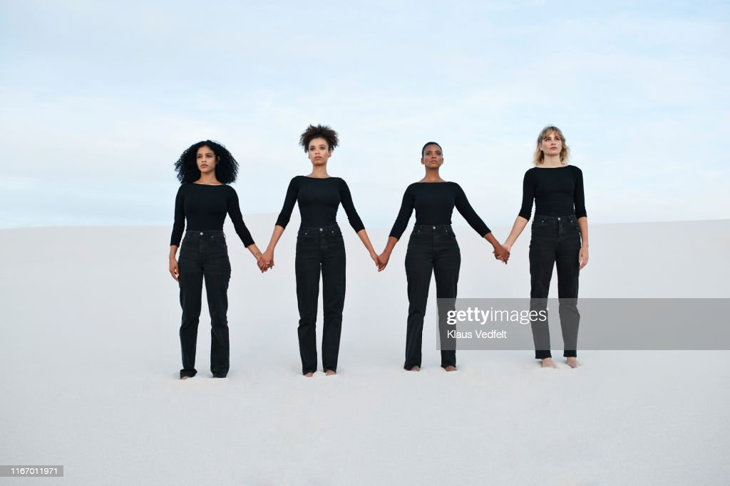 Young female models holding hands while walking at desert during sunset : Stock Photo