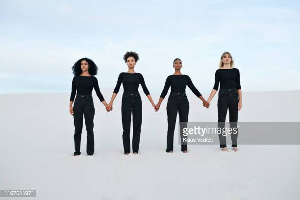 young female models holding hands while walking at desert during sunset - solo donne foto e immagini stock
