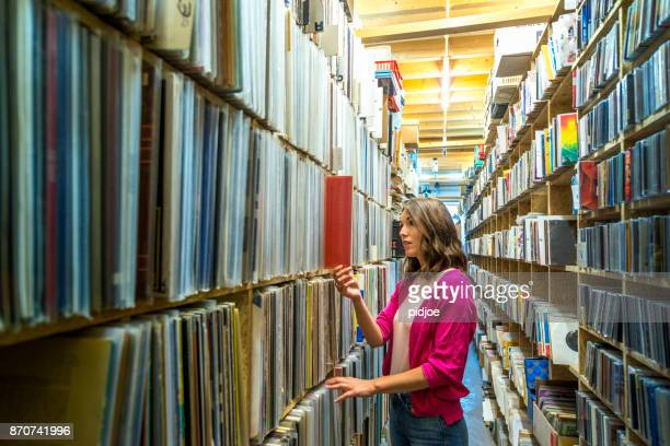 Young female music fan searching  in large vinyl record collection, wide shot