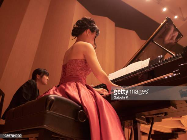 young female musician playing piano concert