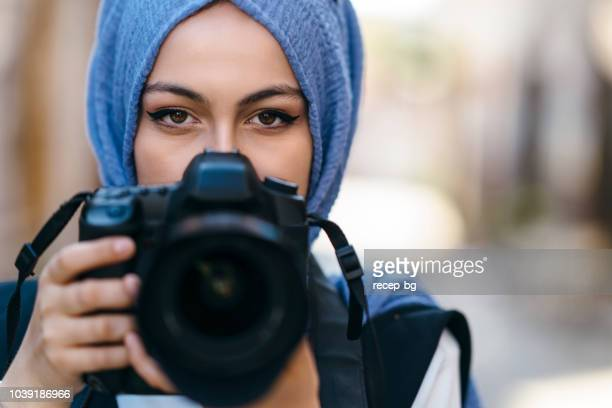 young female muslim tourist taking photos - photographer stock photos and pictures
