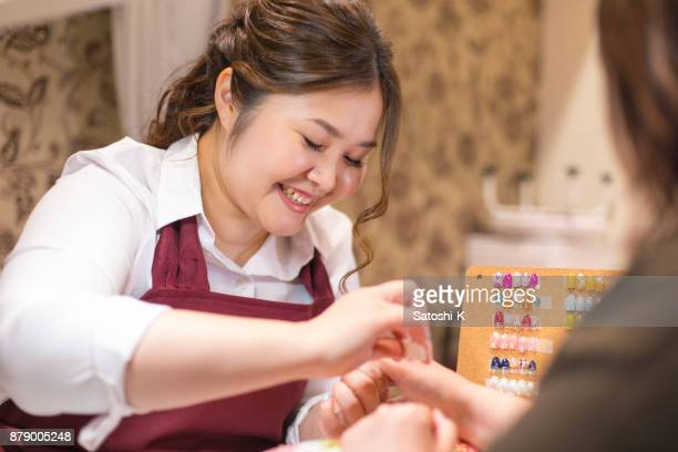 young female nailist polishing client's nails - nail salon stock pictures, royalty-free photos & images