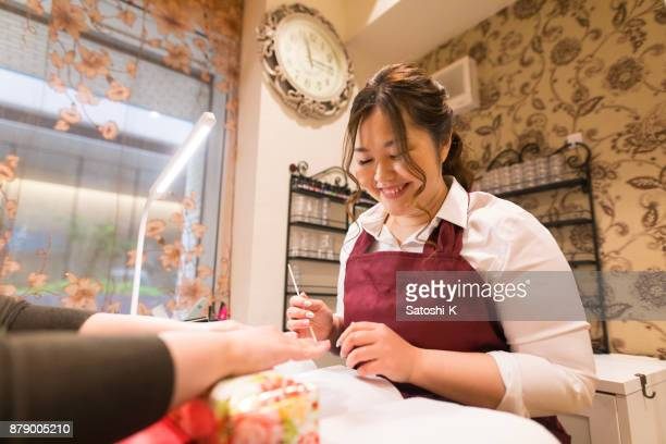 Young female nailst checking clien'ts nails