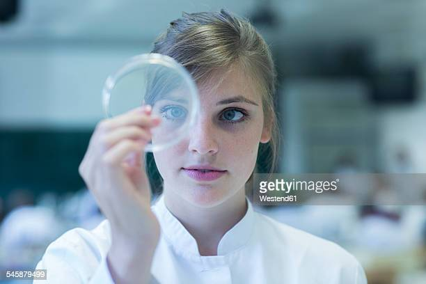 young female natural scientist watching bacteria culture in petri dish at microbiology laboratory - laborkittel stock-fotos und bilder