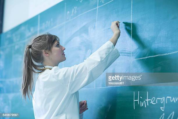 Young female natural scientist writing on blackboard
