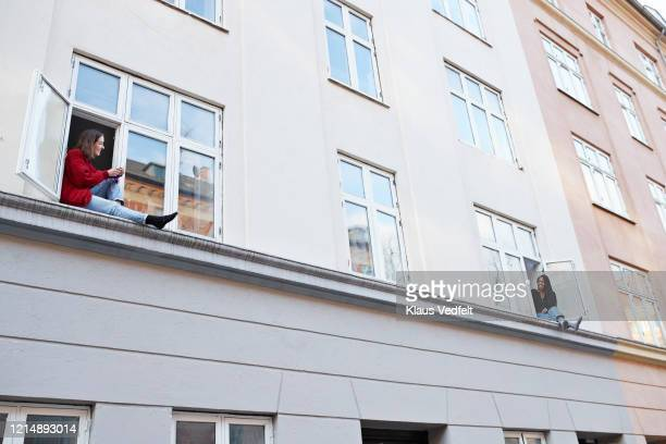 young female neighbors talking from apartment windows - separation stock pictures, royalty-free photos & images