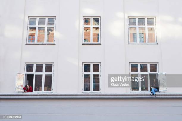 young female neighbors talking from apartment windows - lockdown stockfoto's en -beelden