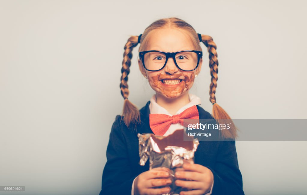 Young Female Nerd Eating Chocolate Bar : Stock Photo