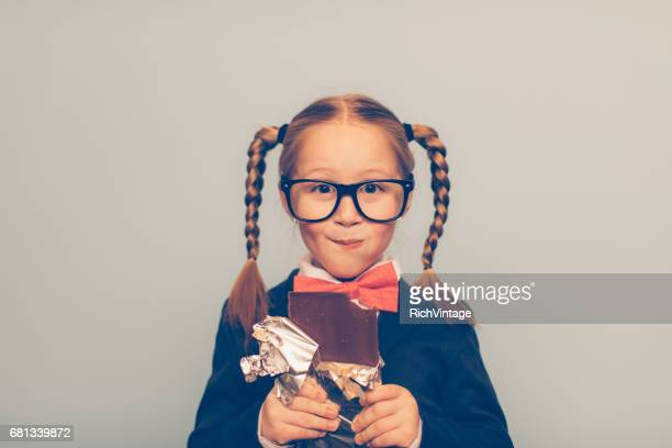 young female nerd eats chocolate bar - girl nerd hairstyles stock photos and pictures
