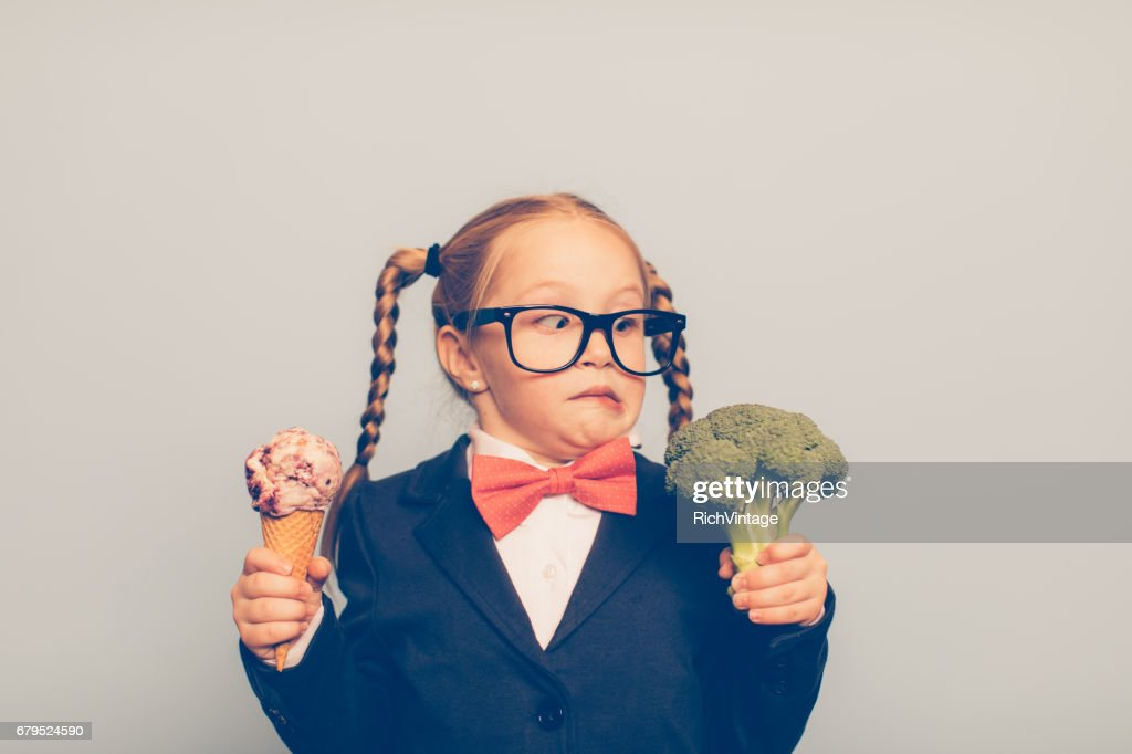 Young Female Nerd Holds Ice Cream and Broccoli : Stock Photo