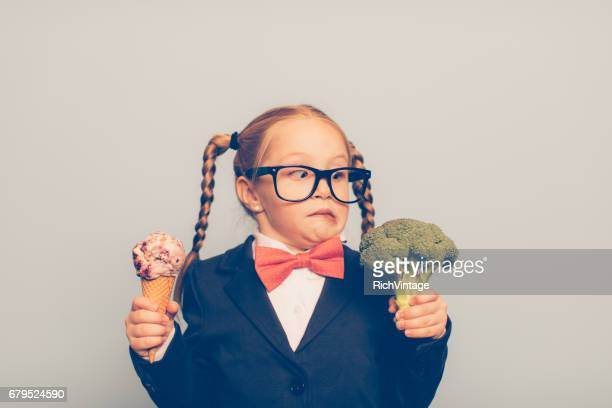 young female nerd holds ice cream and broccoli - practical joke stock photos and pictures