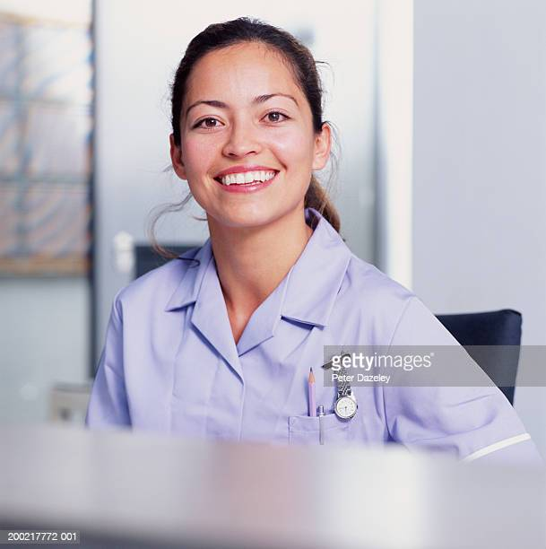 young female nurse behind desk, smiling, portrait - medical receptionist uniforms - fotografias e filmes do acervo