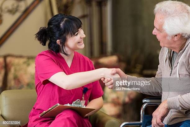 Young female nurse greets new senior male patient
