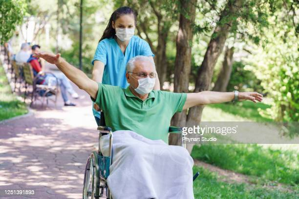 young female nurse with disabled in the garden - wheelchair stock pictures, royalty-free photos & images