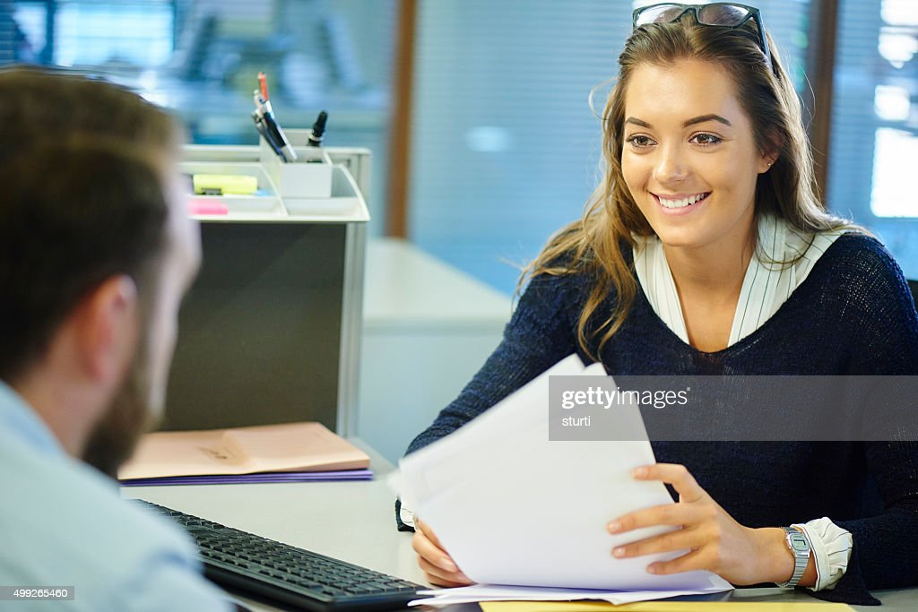 young female office worker chatting to a colleague : Stock Photo