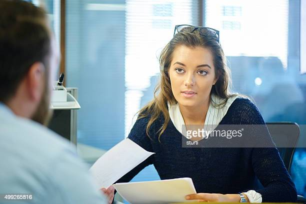 Junge weibliche Büroangestellter Plaudern an einen Kollegen