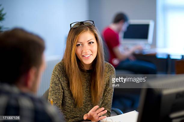 young female office worker chatting to colleague