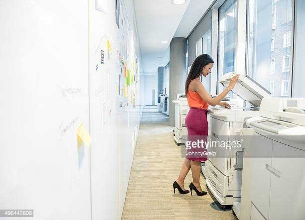 Young female office worker using photocopier
